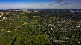 Stadt im Wald nahe dem Fluss mit Kumuluswolken lizenzfreie stockfotos