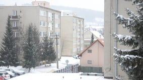 Stadt im Winter, schneit es an der Straße, flache Häuser, Bäume und Autos, irgendein Wanderer geht auf Fußweg stock footage
