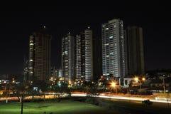 Stadt mit wenigen Gebäuden und vielen Lichtern von Autos auf der Straße verwischt Stockbilder