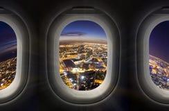 Stadt nachts durch Flugzeugfenster Stockfotografie