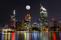 Stadt-Szene mit dem Mond, der über Ho Chi Minh Stadt zentrales Geschäftsgebiet um Nacht sich erhöht lizenzfreies stockfoto