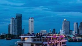 Stadt Timelapse - Bangkoks von hohen Aufstiegs-Gebäuden bei Sonnenuntergang mit beleuchteten Booten auf dem Fluss stock video