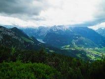 Stadt unter den alpinen Bergen stockbild