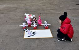 Stadt-Weihnachtsmarkt Ein kleines Mädchen mit einem roten Mantel und einem schwarzen Hut betrachtet die Spielwaren im Straße La C stockfotos