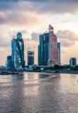 Stadt-Wolkenkratzer im Bau bei Sonnenuntergang mit Wolken über einem Fluss lizenzfreie stockbilder