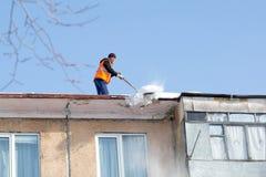 Stadt Yasny, RUSSLAND, am 20. Februar 2019 Arbeitskraft säubert das Dach eines mehrstöckigen Gebäudes redaktionell stockfotografie