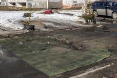 Stadtbewohner bedeckten Gruben der schrecklichen Straße mit alten Teppichen im Frühjahr lizenzfreies stockfoto