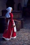 Stadtbewohnerin im roten Kleid mit einem Schutzblech und im Begleiter auf der Straße stockbilder