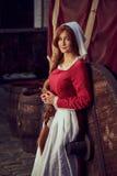Stadtbewohnerin im roten Kleid mit einem Schutzblech und im Begleiter auf der Straße lizenzfreie stockfotografie
