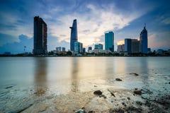 Stadtbild in der Reflexion von Ho Chi Minh-Stadt bei schönem Sonnenuntergang, angesehen über Saigon-Fluss Lizenzfreie Stockbilder