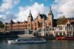 Stadtbild des zentralen Bahnhofs und des alten Stadtkanals mit touristischen Schiffen, Amsterdam, Holland lizenzfreie stockfotografie