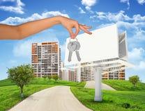 Stadtbild mit der Anschlagtafel und Hand, die Schlüssel halten Lizenzfreies Stockfoto