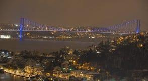 Stadtbild nachts mit glänzender Brücke Lizenzfreie Stockfotografie