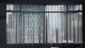 Stadtbildansicht durch modernes Fenster und transperent Vorhänge im Raum stockfoto