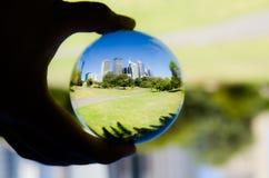 Stadtbildansicht mit Fotografie des grünen botanischen Gartens und des blauen Himmels in der klaren Kristallglaskugel Lizenzfreies Stockbild