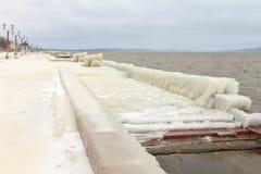 Stadtdamm bedeckt mit Eis nach Wintersturm auf dem See Stockfotos
