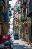 Stadtenge-Straßenansicht Cefalu alte mit den Autos geparkt und den kleinen Balkonen am Morgen Stockbilder