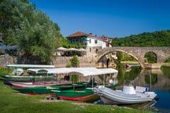 Stadtexkursionsboote Rijekas Crnojevica alte festgemacht Alte Bogenbrücke am Hintergrund Lizenzfreie Stockfotos