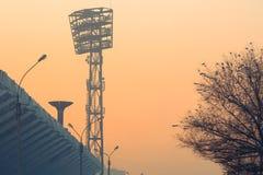 Stadthintergrundschattenbild-Stadionsscheinwerfer, Schüssel für die olympische Fackel und Baum bedeckt mit Schnee bei Sonnenunter Stockfoto