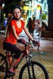 Stadtnachtfahrradfahrt Mädchen, die Fahrradsturzhelm tragen Lizenzfreie Stockfotos