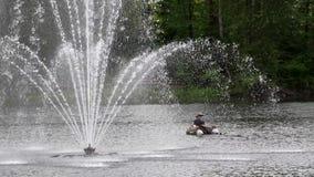 Stadtpark-Brunnenjet im See mit den Leuten, die auf dem Boot fischen stock footage