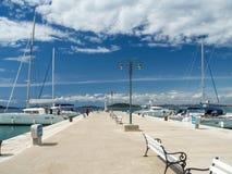 Stadtpier in Zlarin-Insel in Kroatien, tragen Marinesoldaten mit Yachten und Katamarann Lizenzfreies Stockfoto