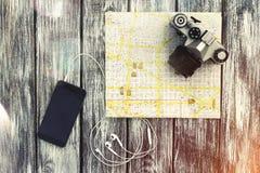 Stadtplan mit einem Smartphone, Kopfhörern und Weinlesekamera Stockbilder