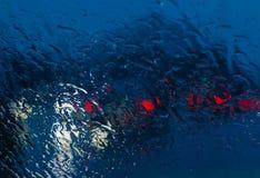 Stadtstraße gesehen durch Regentropfen auf der Autowindschutzscheibe Lizenzfreie Stockfotos