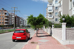 Stadtstraße mit rotem Parkauto am sonnigen Sommertag lizenzfreie stockfotografie