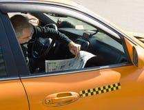 Stadttaxifahrer liest eine Zeitung im Auto während des Restes Lizenzfreie Stockfotografie