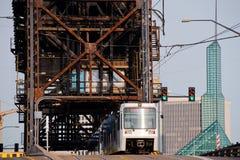 Stadttram auf großer Fachwerkbrücke mit modernen Gebäuden Lizenzfreie Stockbilder