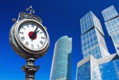Stadtuhr auf dem Hintergrund von modernen Wolkenkratzern Lizenzfreies Stockbild
