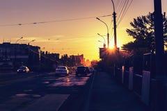 Stadtverkehr, Autos auf der Brücke, schöner Abendsonnenuntergang Stockfotos