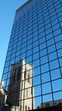 Stadtwolkenkratzer mit reflektierenden Fenstern des Spiegels an einem Tag des blauen Himmels Stockfotografie