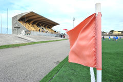 Stadium red flag. Synthetic grass football stadium with a corner kick flag in the foreground stock photo