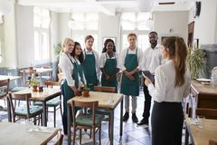 Staff Attending Team Meeting In Empty Dining Room stock image