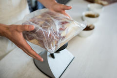 Staff checking the weight of meat packet at counter Royalty Free Stock Images