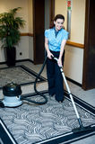 Staff cleaning carpet with a vacuum cleaner. Smiling and enjoying her work Royalty Free Stock Photo
