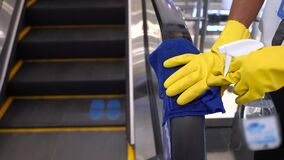 Staff cleaning the escalator hand rail in department store to prevent the spread of pandemic Covid-19 and Coronavirus, healthcare