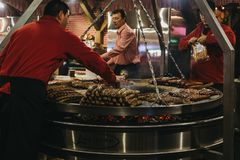 Staff cooking german sausages at Winter Wonderland, London, UK Stock Image