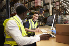 Staff discuss warehouse logistics in an on-site office Stock Image