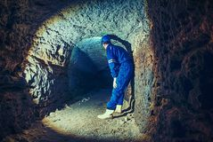 Staff do job in natural underground dome. Man with the illuminated headlight looks Royalty Free Stock Photo