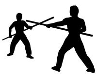 Staff Fighting. Two Martial Artists facing off with long staves Royalty Free Stock Images