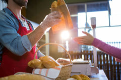Staff giving packet bread to customer Royalty Free Stock Photos