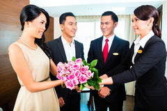 Staff greeting guests in Asian hotel. Staff greeting guests in hotel Stock Photos