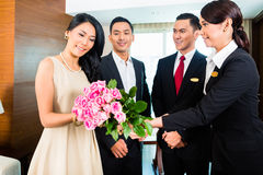 Staff greeting guests in Asian hotel Stock Photo