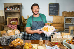 Staff holding bakery snacks at counter. Portrait of staff holding bakery snacks at counter in bakery shop royalty free stock photos