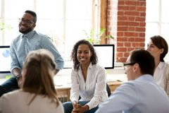 Staff of international company sitting in office during business seminar. Multiracial international company staff sitting together in office room during business stock photography