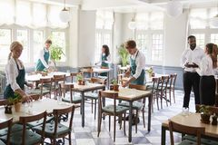 Staff Laying Tables In Empty Restaurant stock image