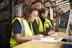 Staff managing warehouse logistics in an on-site office Stock Image